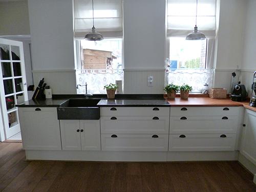 Landelijke maatwerk keuken, voorzien van stenen en houten keukenblad.