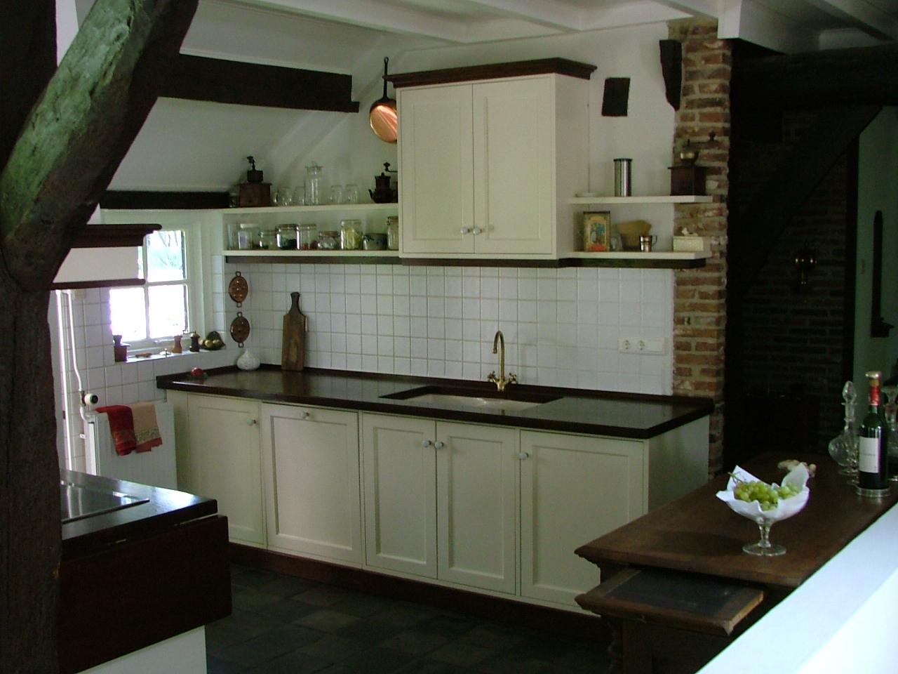 Maatwerk landelijke keuken, uitgevoerd met witte houten kasten en een stenen keukenblad.