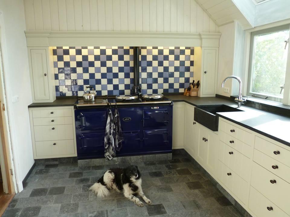 Maatwerk keuken met kasten op verschillende hoogtes en ingebouwde apparatuur.